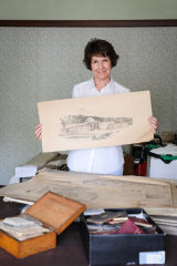 Lucy King with the collection of old architecture plans belonging to her grandfather John Crust who was one of the architects of the Australian War Memorial.