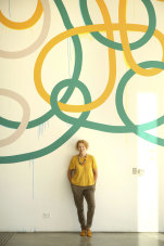 The MCA's Liz Ann Macgregor in front of a wall mural titled 'Triple Tangle' by Artist Gemma Smith.