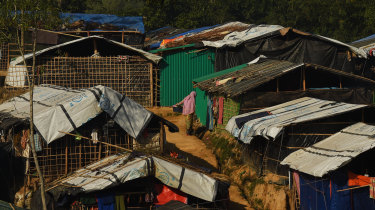 A woman holds a bucket containing clothes as she stands amongst the shelters in Kutupalong refugee camp at Cox's Bazar, home to hundreds of thousands of Rohingya refugees.