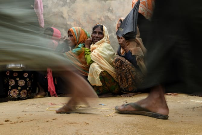 Rohingya refugee women wait in their line as the men in their line run past for a meal provided by a Turkish aid agency.