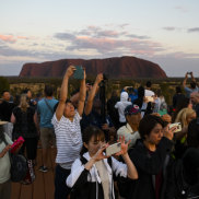 Tourists taking photographs of the rising sun near Uluru on October 12.