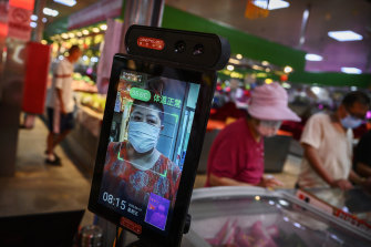 A woman has her temperature checked by thermal imaging at a local market in Beijing.