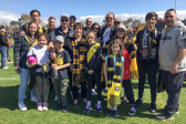Jenny Kefalas, centre front with scarf, brought a large group of relatives to the Richmond Football Club family day at Punt Road Oval.