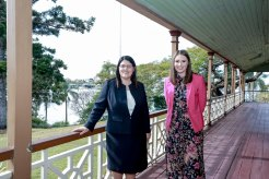 Heritage Minister Meaghan Scanlan (right) with local MP and Education Minister Grace Grace on the veranda of Newstead House as it begins a $5 million restoration.