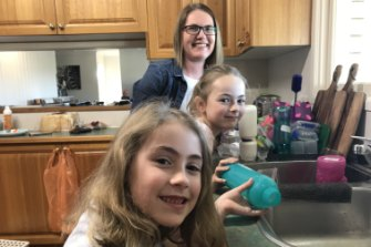 Piper (front), Mackenna and Kristy Robertson doing the dishes as part of their pocket money scheme.