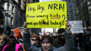 "A demonstrator holds a sign that reads ""Hey, Hey, NRA! How Many Kids Have You Killed Today,"" while gathering on 6th Avenue during the March For Our Lives in New York City on Saturday."