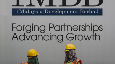 Construction workers chat in front of a billboard for state investment fund 1 Malaysia Development Berhad (1MDB) at the fund's flagship Tun Razak Exchange development in Kuala Lumpur, Malaysia.