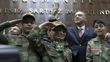 Turkey's President Recep Tayyip Erdogan salutes with children in commando uniforms as he addresses the members of his ruling party at the parliament in Ankara on Tuesday.