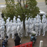 Workers in hazmat suits prepare to administer COVID-19 tests for employees at Shanghai Pudong International Airport.