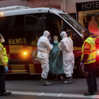 A patient, centre, is transferred to a medicalised hotel during the COVID-19 outbreak in Madrid, Spain.