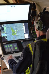 Aircraft Mission Coordinator Chris Hinder operates the search sensor suite.
