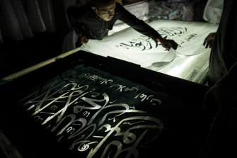 Workers hand-print Taliban flags in a small workshop in Kabul's Jawid market. The flag shop has documented Afghanistan's turbulent history over the decades with its ever-changing merchandise. Now the shop is filled with white Taliban flags.