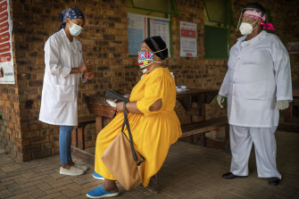 Asnath Masango, right, and Carol Ditshego, left, brief a patient before giving her a COVID-19 test at the Ndlovu clinic in Elandsdoorn, as part of the Johnson & Johnson vaccination trial.
