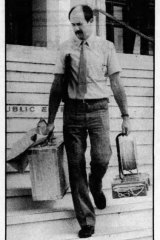 Constable Phil Case carries out the hoax bomb in a paper bag from Parliament House in Canberra.