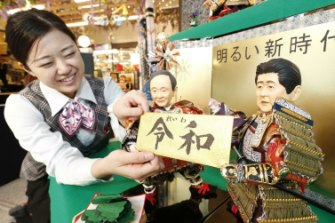 "A shop worker arranges dolls representing Japanese politicians in a display to celebrate Japan's new ""Reiwa"" imperial era."