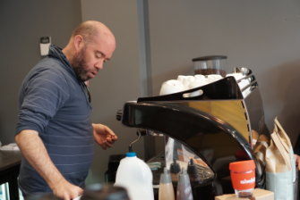 Poised for success: Barista Andy Kenny serves a crowd at the launch of BusyBeans Cafe.