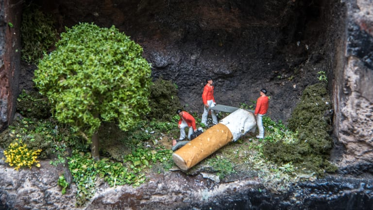 A tiny man is crushed by a cigarette in one of the installations by Ms Sonntag.