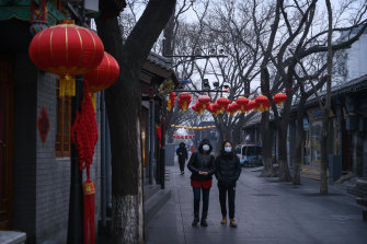 Chinese women walk in a usually busy shopping and tourist area during the Chinese New Year holiday in Beijing. The holiday has been extended to limit travel after the coronavirus outbreak.