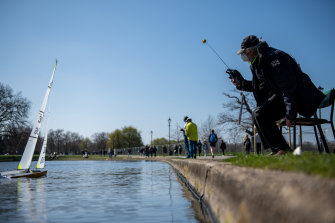 A man wearing a face mask operates a remote control boat on a pond in Clapham Common in London. The British government has eased rules on socialising, permitting groups of six people (or more if limited to two households) to meet outdoors.