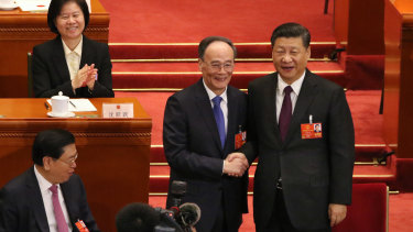 Xi Jinping shakes hands with newly elected vice-president Wang Qishan at National People's Congress.