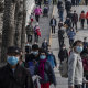 People wear protective masks as they walk while enjoying the spring weather on April 5, 2020  at a park in Beijing.