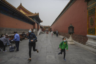 A mother and child run through the Forbidden City in Beijing.