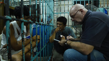 Murdoch, with Filipino journalist Bernard Testa, interviews a survivor of a shooting during a police drug raid, in a holding cell at a police station in Manila in 2016.