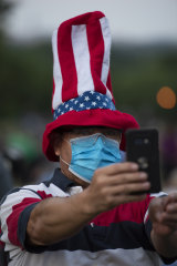 A person takes a photo while waiting for fireworks on the National Mall in Washington, on July 4, 2020.