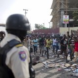 A police officer looks on as a crowd enters the Delimart supermarket complex, which had been burned during two days of protests against a planned hike in fuel prices in Port-au-Prince,