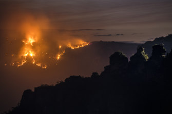 The Ruined Castle fire burns under strong westerly winds in front of Mount Solitary at Echo Point in Katoomba.