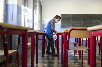 A school worker disinfects desks at the end of the day.
