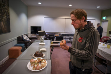 Michael, pictured at dinner,  says sleeping at the church means he is close to family in the eastern suburbs.