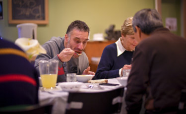 Glenn eating dinner with volunteers who made and served dinner at Heathmont Baptist Church.