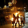 An Israeli police water cannon is deployed near the Damascus Gate to the Old City of Jerusalem as a fire burns during clashes between police and Palestinian protesters on Monday.