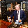 West Australian Premier Mark McGowan cleans the bar with  Bar Bizu owner Jimmy Durante.
