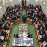 Queensland MPs standing to indicate their vote in favour of the Palaszczuk government's voluntary assisted dying bill at the end of its second reading debate on Thursday.