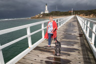 Perks of the job: House-sitter Petrina Dakin takes puppy Winnie for a walk at the Point Lonsdale pier.
