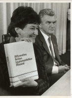 Senator Susan Ryan with Prime Minister Bob Hawke as she holds the Affirmative Action Implementation Manual, June 1984.