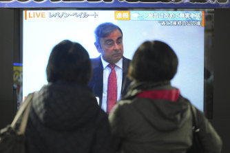People in Tokyo watch a TV showing a live broadcast of Carlos Ghosn's statement.