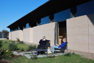 Rob and Sally Hawkins sitting near the massive rammed earth wall on the eastern side of the Mystery Bay home. The house, designed by their son, architect Jack Hawkins, is one of the finalists in this year's Australian Institute of Architects' NSW award for best new house.