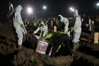 Workers bury a COVID-19 victim at Rorotan Cemetery in Jakarta, Indonesia.