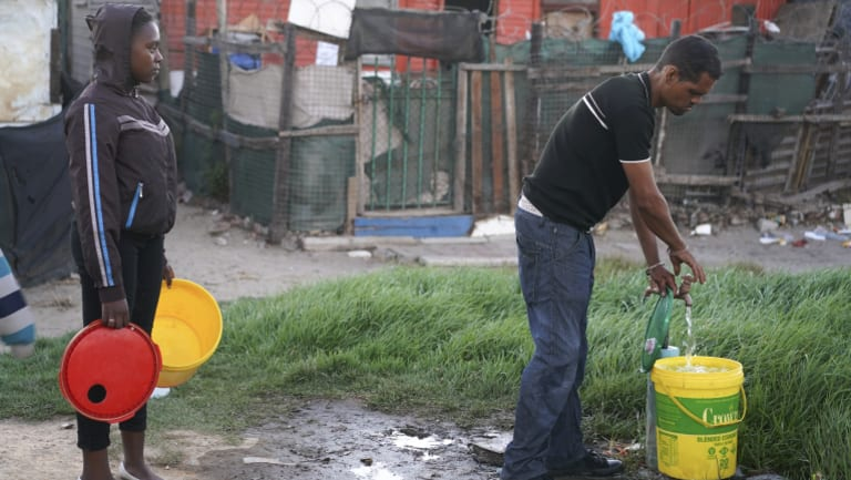 Residents collect water from a communal tap in an informal settlement in Mitchells Plain outside of Cape Town.