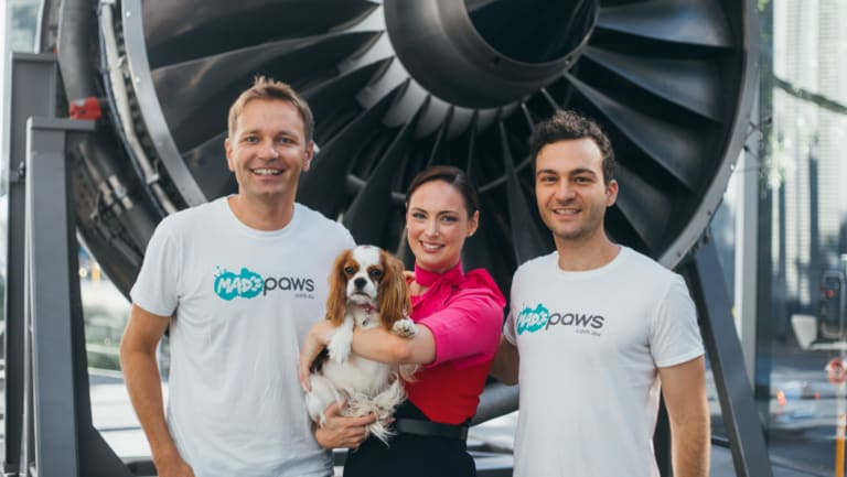 Mad Paws founders Jan Pacas and Alexis Soulopoulos with a Qantas staff member.