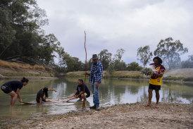 Barkandji artist Badger Bates launching the Barkandji Canoe which was created through the Art Gallery of New South Wales Djamu Indigenous Art Education Program. Wilcannia,