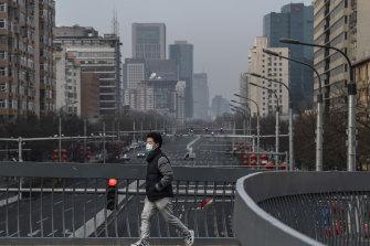 A man wears a protective mask as he crosses a footbridge over a nearly empty road in a residential neighbourhood in Beijing.