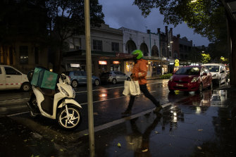 A food delivery rider braves the wintry conditions in Surry Hills on Friday night.