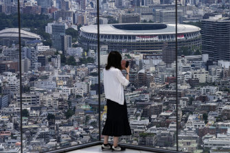 A person takes a picture from an observation deck of the National Stadium, where the Opening Ceremony will be held on July 23.
