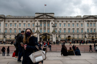 A woman wears a face mask as she visits Buckingham Palace as the outbreak of coronavirus intensifies.