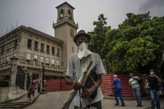 A pedestrian wearing a makeshift face mask amid the new coronavirus pandemic, walks past the Central Railway Station, in Havana, Cuba.