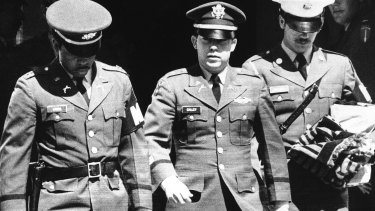 Flanked by two military policemen,  William Calley leaves court after he was sentenced to life imprisonment in 1971.